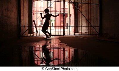 Young woman performs modern dance near lattice gate