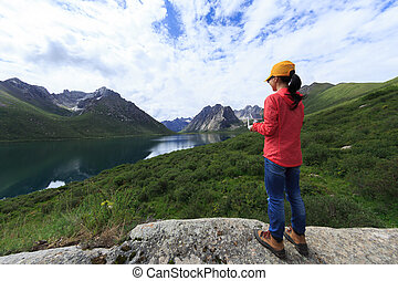 young woman photographer flying drone outdoors