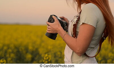 Young woman photographer holding a camera, close-up