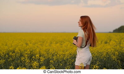 Young woman photographer in a blooming field