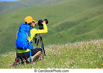 young woman photographer taking photo outdoors