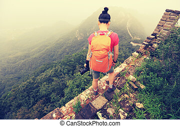 young woman photographer with camera on top of great wall