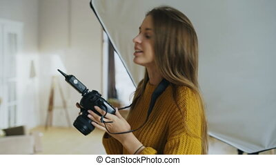 Young woman photographer working in a photo studio taking photos of male model on digital camera