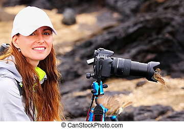 Young woman photographing on Santiago Island with Galapagos flycatcher on her lens hood, Galapagos National Park, Ecuador