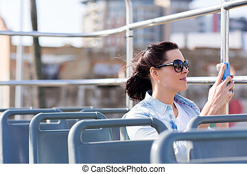 young woman photographing the city using smart phone