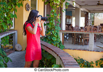 Young woman photographs the stunning view from cozy balcony