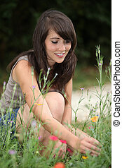 Young woman picking wildflowers from the side of a pathway