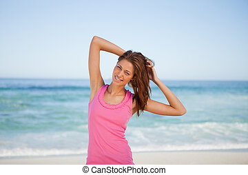 Young woman placing her hands behind her head on the beach