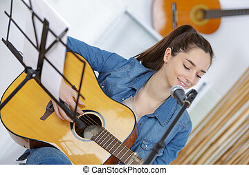 young woman play with guitar at home