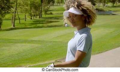 Young woman player walking with a golf club