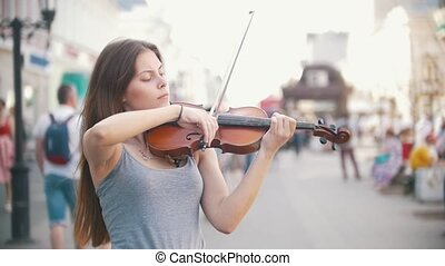 Young woman playing a violin at the pedestrian street, close...