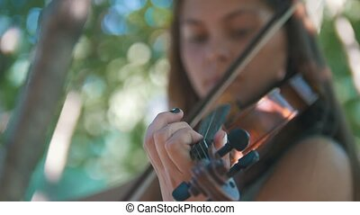 Young woman playing a violin standing on the grass in the park at sunset