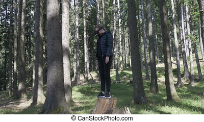 Young woman playing a virtual reality game outdoor in the forest with vr headset