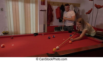 Young woman playing billiard with her boyfriend happy to hit the target ball into the hole
