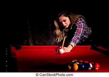 Young woman playing billiards in the dark billiard club