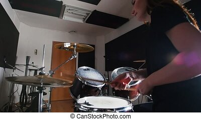 Young woman playing drums in the Studio