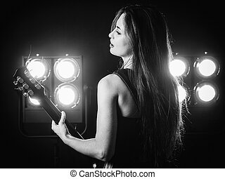 Young woman playing electric guitar on stage