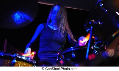 Young woman playing electronic drums on stage. Concert - red Neon light.