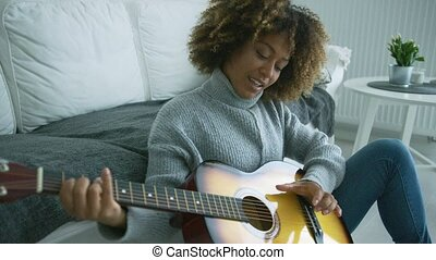 Young woman playing guitar at home - Charming young model in...