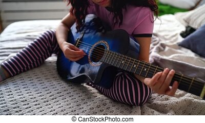 Young woman playing guitar in bedroom. Close-up female hand playing a guitar string.