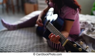 She enjoys her spare time. Beautiful girl play guitar in a cozy bedroom