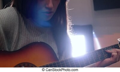 Young woman playing guitar in recording studio. Close up