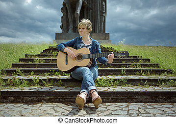 Young woman playing guitar on steps near the monument in windy weather