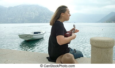 Young woman playing guitar sitting on pier sea in summer day.