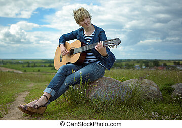 Young woman playing guitar sitting on rock in the field in windy weather