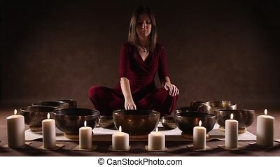 Young woman playing Tibetan singing bowls in front of brown...