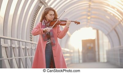 Young woman playing violin on the overhead passage, autumn