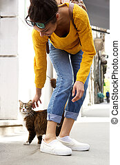 Young woman playing with a cat on city street