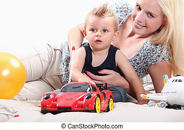 Young woman playing with a little boy and his toys