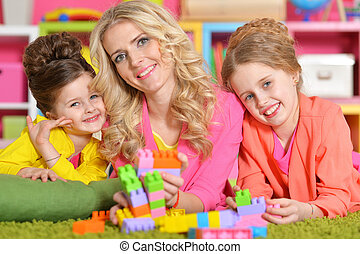 young woman playing with daughters