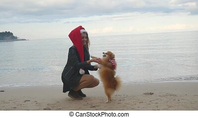 Young happy woman dancing with Pomeranian Spitz outdoors near the sea. Both in Santa hats. New Year holiday concept.