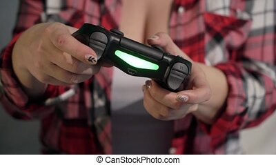 Young woman plays video game using a gamepad. Closeup.