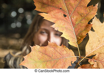 Young woman plays with branches with autumn leaves