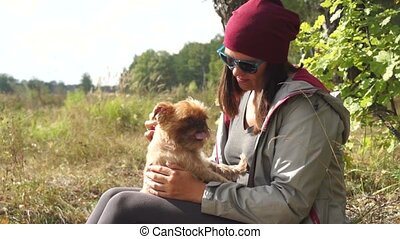 Young woman plays with small dog Griffon Bruxellois breed...