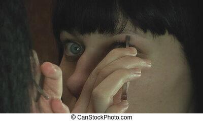 Young woman plucking eyebrows with tweezers