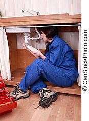 Young woman plumber fitting the waste on a kitchen sink