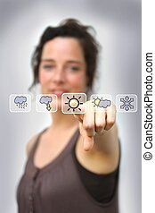 young woman pointing at a digital weather interface