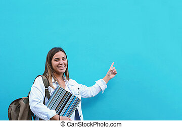 Young woman pointing at copy space