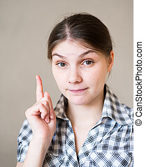 young woman pointing at copy space with index finger