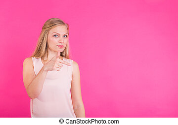 Young woman pointing at pink background with copy space