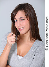 Young woman pointing at with finger