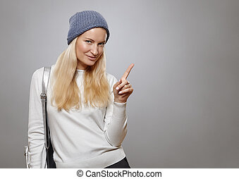 Young woman pointing finger at copy space.