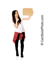 Young woman pointing on a cardboard.