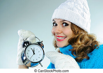 Young woman pointing on alarm clock