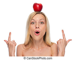 Young woman pointing on apple on head