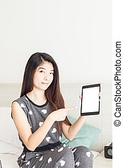 Young woman pointing on tablet